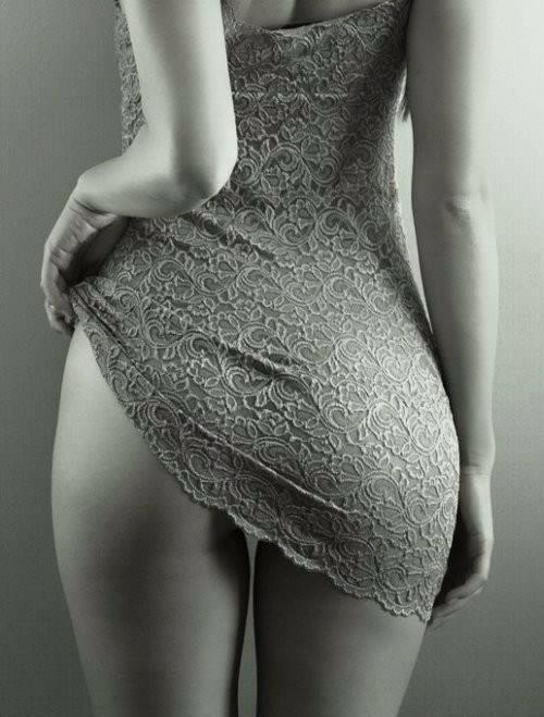 Женская сексуальность - девушка стоит спиной, задирает кружевное платье, обнаженное бедро